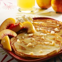Fluffy pancakes with sliced white nectarine and honey drizzle